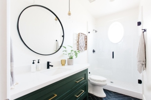 black bathroom cabinet, black trim, circle mirror and white marble shower