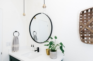 white bathroom walls with black circle mirror, brass and glass pendant lights