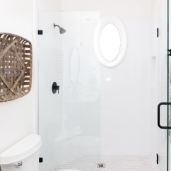 white marble shower with black trim, woven basket wall decor, white herringbone tile