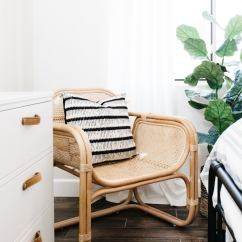 wicker chair with black and white striped pillow and green plant