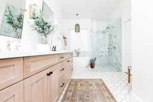 master bathroom double vanity in oak with tribal print rug and marble tile and soaker tub