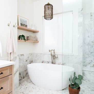 white modern soaker tub with marble flooring and back splash