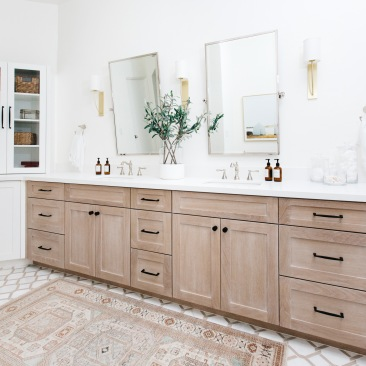 master bathroom double vanity in oak with basketweave tile and tribal print rug and glass medicine cabinet
