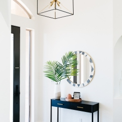 black and brass cube lighting with circle tribal print mirror black entry table palm leaves in vase