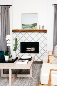 diamond patterned white and gray tiled fire place with rough wood mantle textured black and white rug