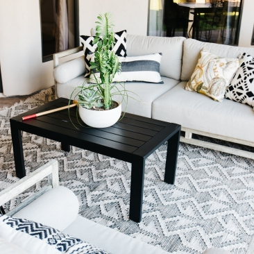 worn white modern outdoor couch with black and white tribal accessories potted cactus in bowl black coffee table wood stump side table