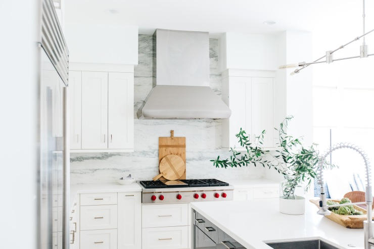 gray and white marble back splash white quartz countertops white cabinets steel hood