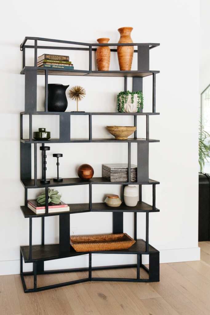 Modern angular iron book shelf filled with interesting shaped decor