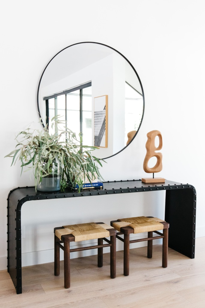 modern waterfall edge side table with small stools and large round mirror