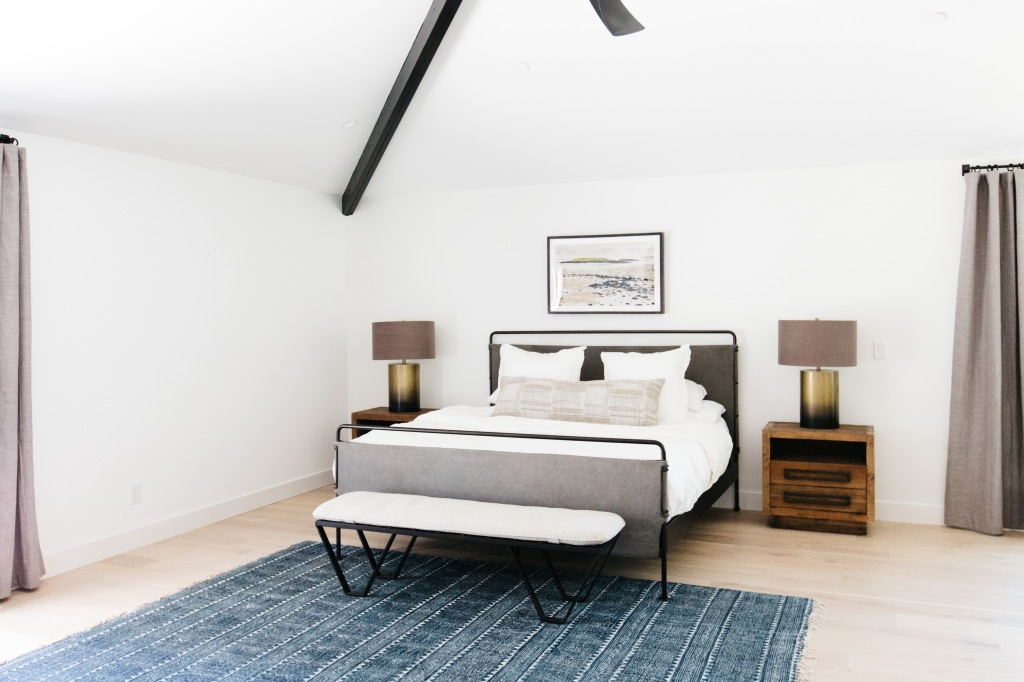 modern simple master bedroom with iron bed and wooden furniture