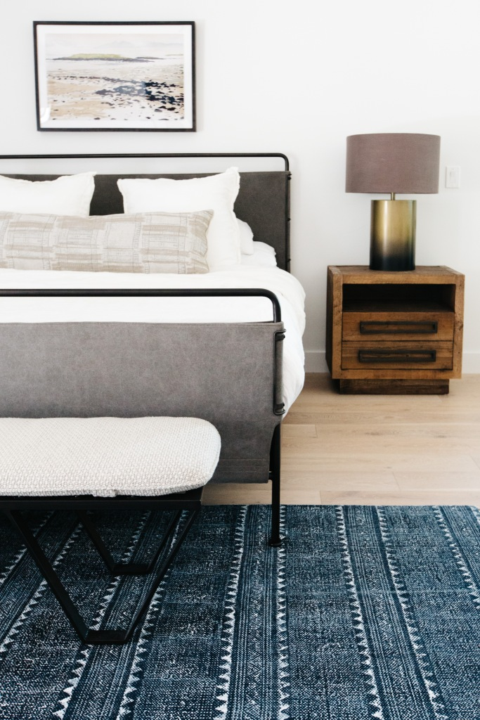 rn simple master bedroom with iron bed and wooden furniture blue gray tribal rug