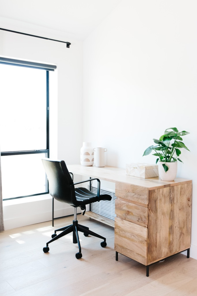 modern light colored wooden desk with sleek black leather chair