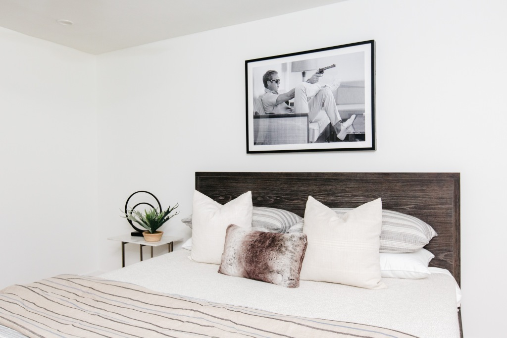 guest bedroom with modern shaped gray wood bed red rug black and white artwork