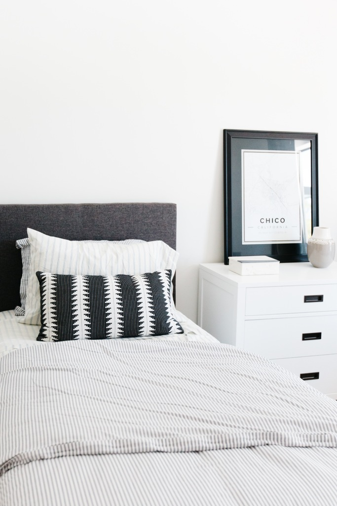 guest bedroom with modern tweed gray headboard black and white artwork